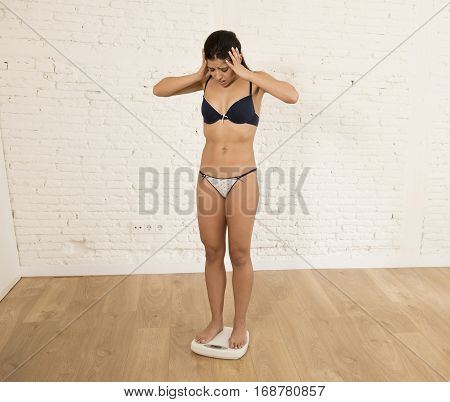 young fit skinny woman or teen girl checking body weight on scale finding herself fat looking desperate obsessed with overweight and weight loss in anorexia and bulimia nutrition disorder