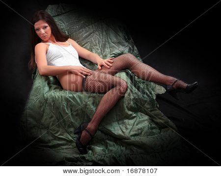 Pretty woman with long slim legs in net nylons. Vintage style low key photography. Great for calendar