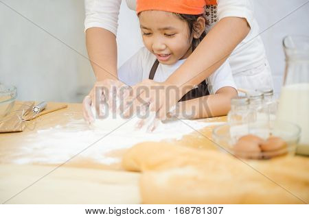 Close up shot of Asian little girl with hands of mother kneading the dough for making the bakery on white background focus on face