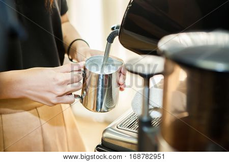 barista make a cappuccino or latte steaming and frothing milk