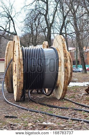 Wooden coil of electric cable and optical fibres on the street construction site