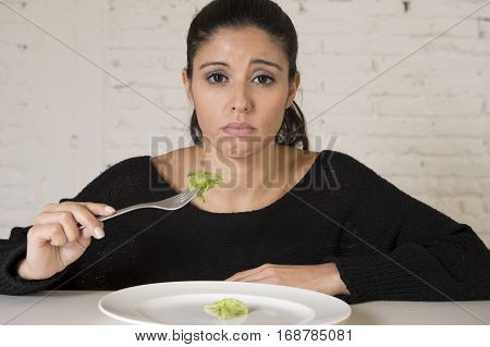 young woman or teen with fork eating dish with ridiculous little lettuce as her food symbol of crazy diet in nutrition disorder concept anorexia and bulimia and refusing to eat in diet calories obsession