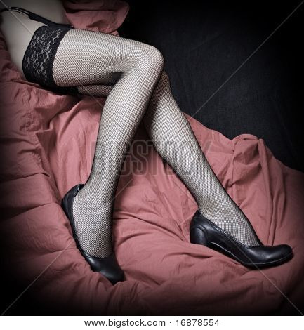 Beautiful slim legs in black nylons on a pink background. Vintage style photography - great for calendar. poster