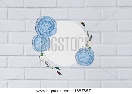 White Background With Handmade Gentle Blue Ranunculus Flowers, Roses and Crystals, Lying Flat on the White Brick Wall, Top View. Have a Empty Circle Place For Your Text.