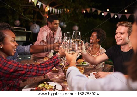 Friends and family toasting at garden dinner party, close up