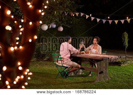 Young black couple make a toast at dinner in a garden