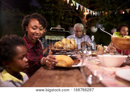 Young black mother serving her son food at a family barbecue