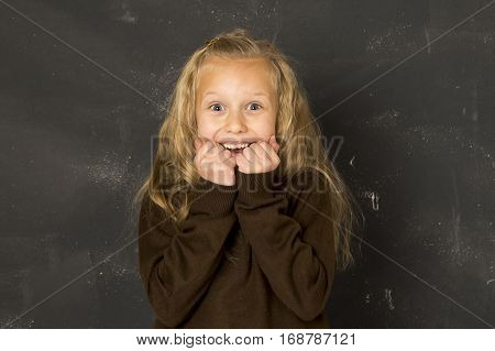 young beautiful blond sweet schoolgirl in uniform laughing excited in front of school class blackboard smiling happy with blank copy space in education and back to school concept