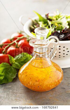 Italian vinaigrette dressing in a vintage bottle with fresh vegetables on the table