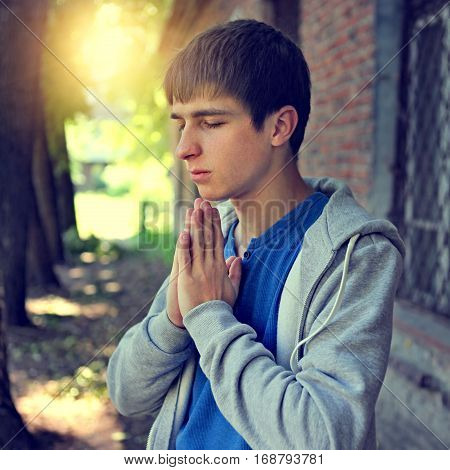 Toned Photo of Young Man praying on the Brick Building Background