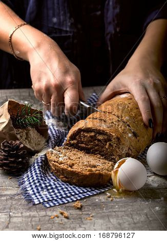 The baker slicing a knife breads. Nearby egg and flour. The concept of baking