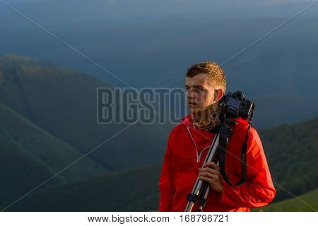 photographer holding a tripod and camera while looking out on mountain
