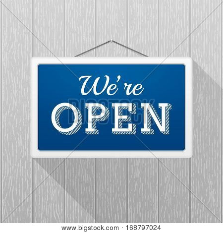 Simple blue sign with text 'we're open' hanging on a gray wooden wall. Wood texture with vertical stripes rustic panels. Creative business interior template for shop store supermarket.