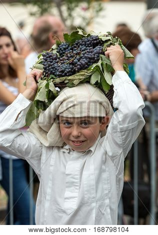 FUNCHAL MADEIRA PORTUGAL - SEPTEMBER 4 2016: Boy carry the basket of grapes in traditional costume durnig historical and ethnographic parade of Madeira Wine Festival in Funchal. Madeira Portugall