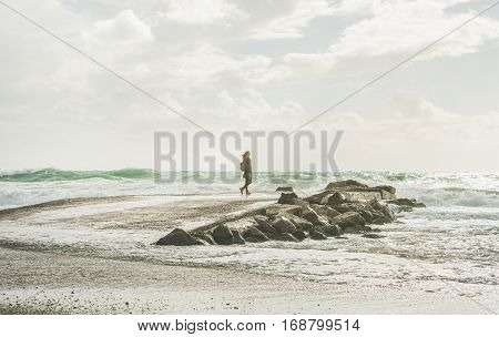 Young woman traveler standing on pier surrounded by stones and looking at waves of stormy Mediterranean sea in winter, Alanya, Turlkey