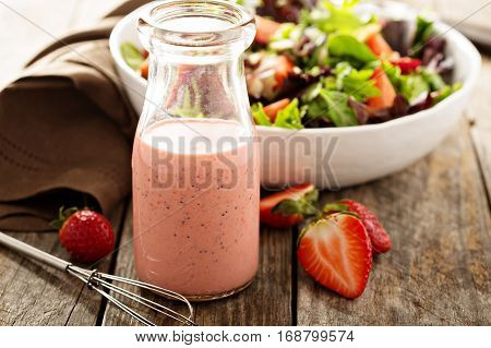 Strawberry poppy seed salad dressing in a glass bottle