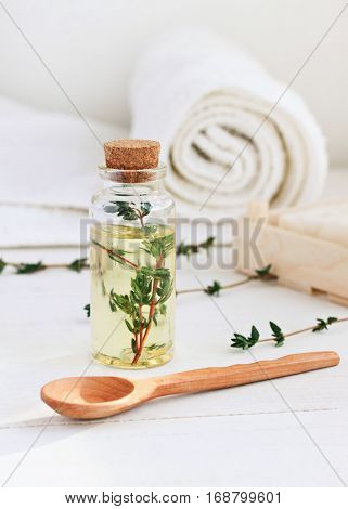 Essential thyme oil in glass bottle, herb sprigs. Natural skincare. Vertical.