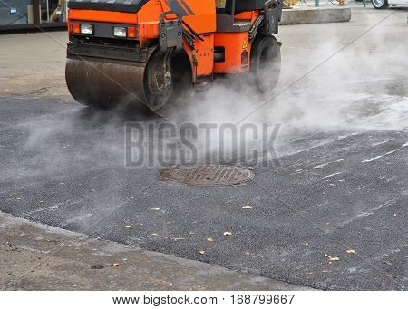 Road repair compactor lays asphalt. Close up on road pavement.