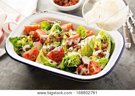 Wedge salad with baby lettuce, cherry tomatoes, bacon and ranch dressing poring over
