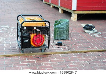 Mobile Generator on the Construction Site Background. Gasoline powered ten horsepower emergency electric generator with Gasoline Canister
