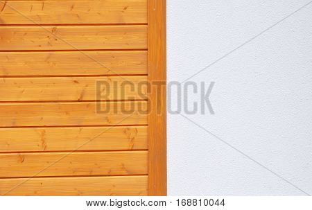 Modern house wall texture of finely slatted natural brown pine wood in a parallel pattern and white stucco used in building decor and construction on facade wall outdoor.
