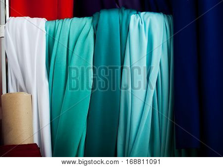 Rolls of textile cloth and tissue of various colours on the market.