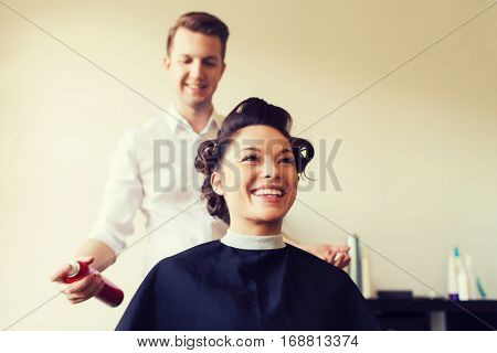 beauty, hairstyle and people concept - happy young woman with hairdresser with hair spray fixating hairdo at salon poster