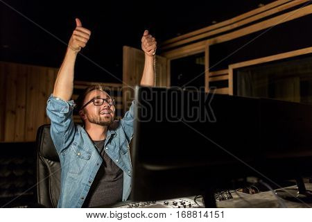 music, technology, gesture and people concept - happy man at mixing console in sound recording studio showing thumbs up