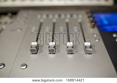 music, technology, electronics and equipment concept - mixing console at sound recording studio