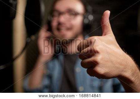 music, show business, people and voice concept - hand of singer showing thumbs up at sound recording studio