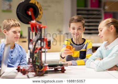 education, children, technology, science and people concept - group of happy kids with 3d printer and plastic detail prototype at robotics school lesson