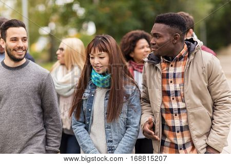 people, friendship, communication and international concept - group of happy friends walking along autumn park
