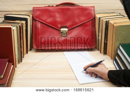 Follow the law. Professional lawyer sitting at the table and signing papers. On a wooden table books documents red briefcase. Copy spase.