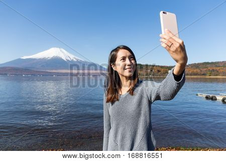 Woman taking photo with Mount Fuji