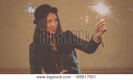 Defocused image of happy girl in hat with burning sparkler in her hands, vintage looking toned shot, instagram color.