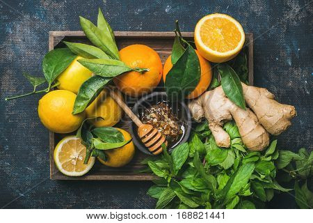 Ingredients for making immunity boosting natural drink. Lemons, oranges, mint, ginger, honey in wooden box over plywood background, top view. Clean eating, healthy lifestyle, detox, dieting concept