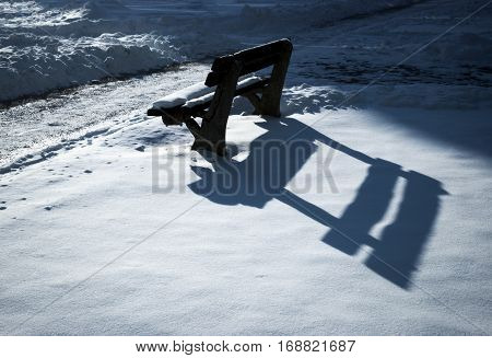 seasonal background shadow on the bench early evening snow