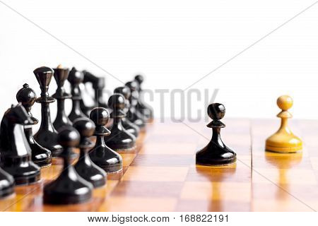 Two pawn staying against full set of black chess pieces. With selective focus on pawn.