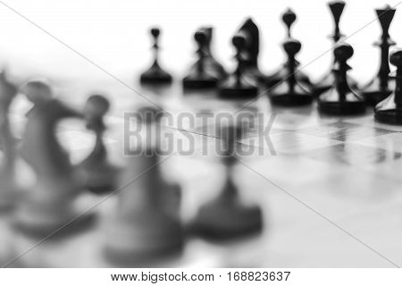 Blurred chess background. Chess set on the chess board. Black and white foto.