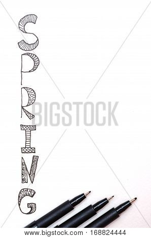 White paper with lettering Spring and three black markers of varying thickness