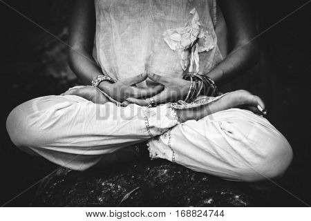 closeup of woman hands and legs in meditative pose practice yoga outdoor shot black and white