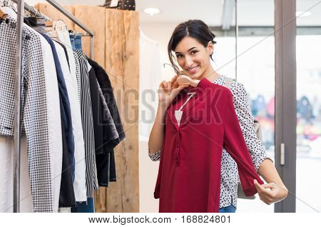 Young smiling woman trying new clothes on mall. Smiling girl shopping in retail outlet for clothes and looking at camera. Portrait of beautiful girl deciding to buy a red blouse.