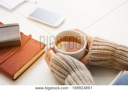 Close up of woman hands holding a cup of lemon tea on table in a winter afternoon. Woman hands holding hot drink on table. Female hands with beige warm sweater holding hot tea with a slice of lemon.