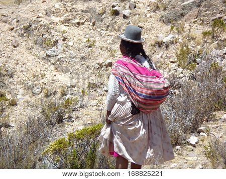 Bolivian woman with a derby hat in the mountain