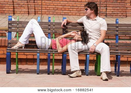 young adult couple  on the bench - man is siting, woman is lying