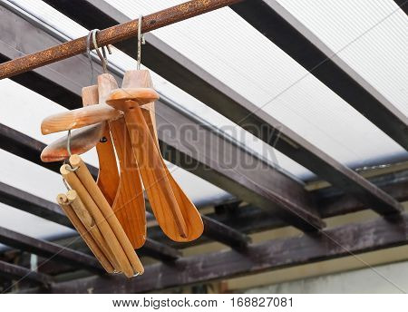Wooden Coat Hangers Hanging on Old Rustic Clothes Rack with Copy Space for Text Decoration.