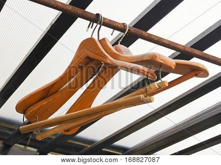 Wooden Coat Hangers Hanging on Old Rustic Clothes Rack.