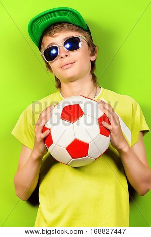 Studio portrait of a cool boy teenager with football over green background.