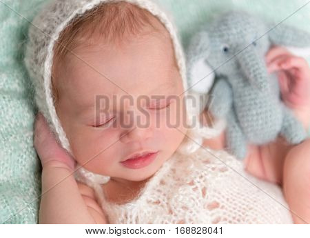 beautiul sleeping newborn baby in hat with toy in hand, closeup
