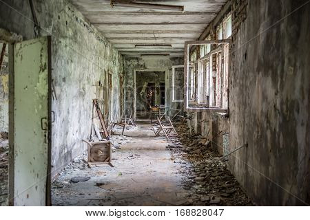 abandoned school corridor with debris and broken chairs and windows in Pripyat